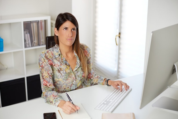 Femme d'affaires fatiguée travaillant avec ordinateur