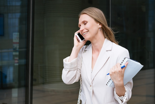 Femme d'affaires ou femme d'affaires prospère prenant des notes et parlant au téléphone portable tout en marchant dehors...