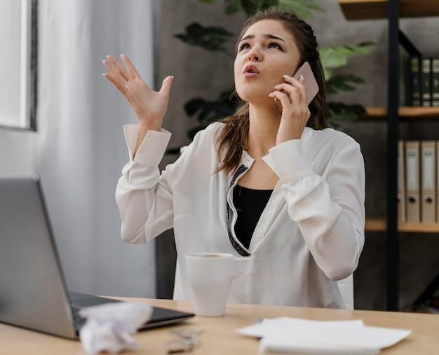Femme d'affaires à la frustration tout en ayant un appel