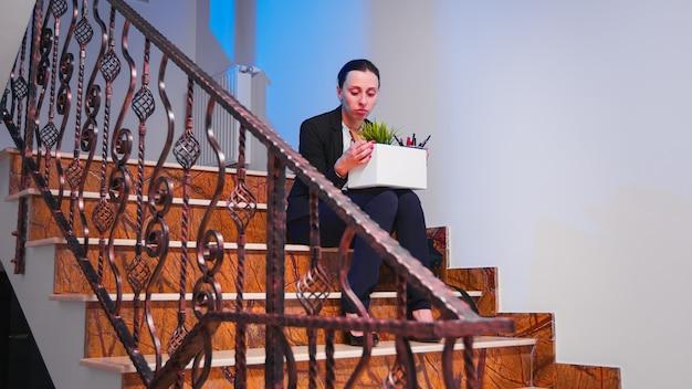 Femme d'affaires frustrée se faire virer assise sur l'escalier du bureau et pleurer en tenant une boîte de trucs. employée se levant dans l'escalier serrant sa collègue dans ses bras, travaillant dans un immeuble financier moderne.