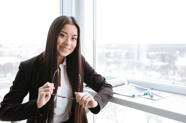 Femme d'affaires gai tenant des lunettes debout près de la fenêtre au bureau