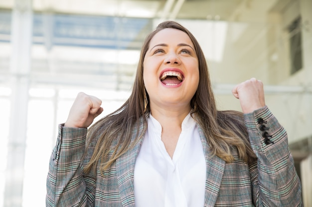 Femme d'affaires gaie célébrant le succès à l'extérieur