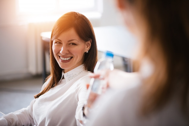 Femme d'affaires gaie donnant une bouteille d'eau plate naturelle à son collègue.