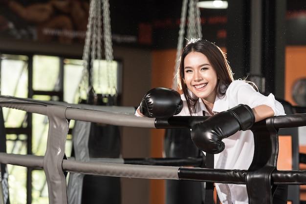 Femme d'affaires et gants de boxe sur le ring de boxe souriant heureux.