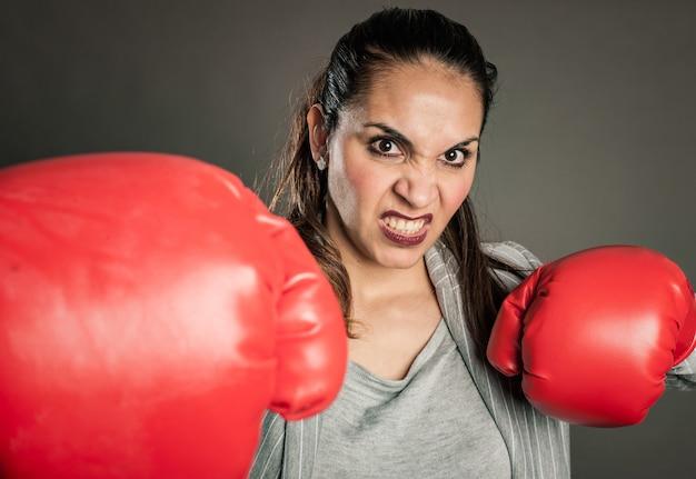 Femme d'affaires avec des gants de boxe rouges