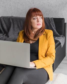 Femme d'affaires grand angle travaillant sur ordinateur portable