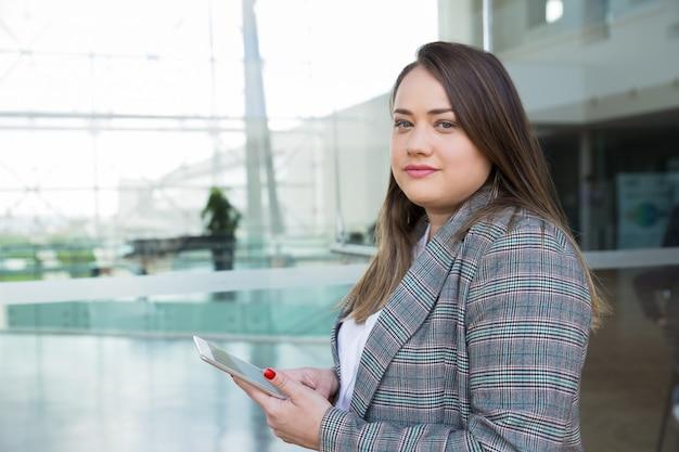 Femme d'affaires graves tenant la tablette à l'extérieur