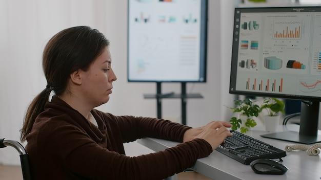 Femme d'affaires handicapée handicapée immobilisée dans un fauteuil roulant travaillant sur un projet financier tapant sur un ordinateur montrant des données en cours d'affichage assises dans un bureau d'affaires de démarrage