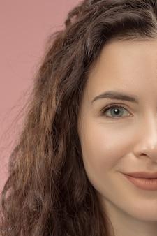 Femme d'affaires heureuse debout et souriant isolé sur fond de studio rose. beau portrait de moitié visage féminin. jeune femme émotionnelle. émotions humaines, concept d'expression faciale. vue de face.