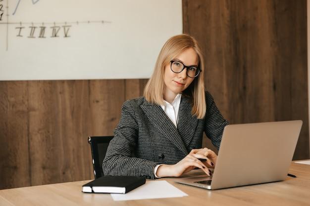 Femme d'affaires heureuse jeune femme d'affaires à l'aide d'ordinateur, surfer sur internet, assis à la table de bureau, en tapant e-mail sur ordinateur portable au lieu de travail