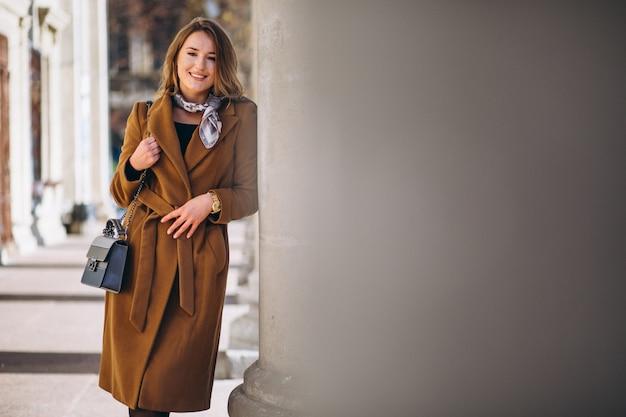 Femme d'affaires heureuse en manteau dans la rue