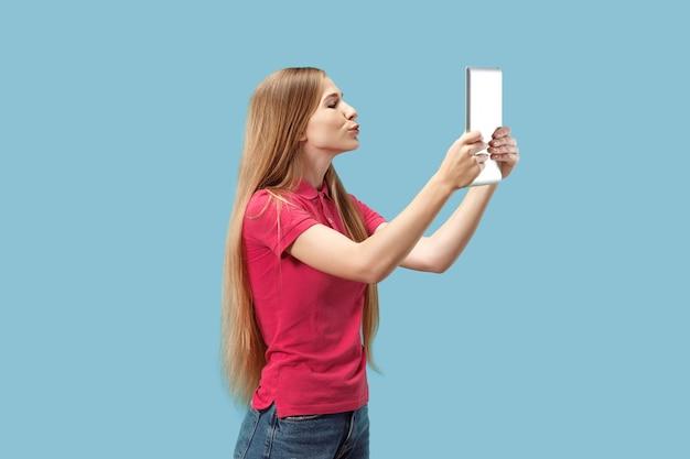 La femme d'affaires heureuse avec ordinateur portable rouge sur bleu