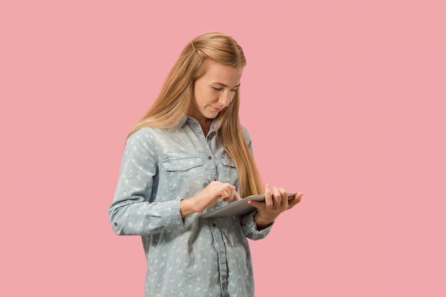 La femme d'affaires heureuse avec ordinateur portable rouge sur rose