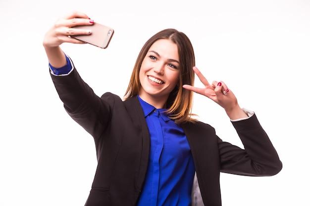 Femme d'affaires heureuse prenant smartphone photo selfie isolé sur mur blanc