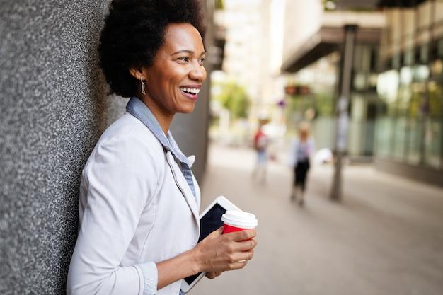 Femme d'affaires heureuse souriante, avocate marchant avec du café en ville