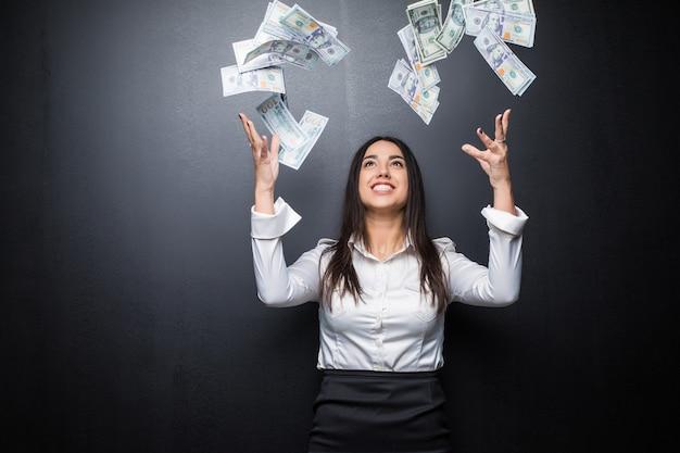 Femme d'affaires heureuse sous une pluie d'argent en dollars isolé sur un mur noir