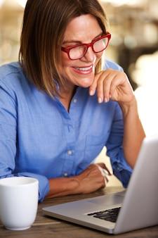 Femme d'affaires heureux assis au bureau avec ordinateur portable