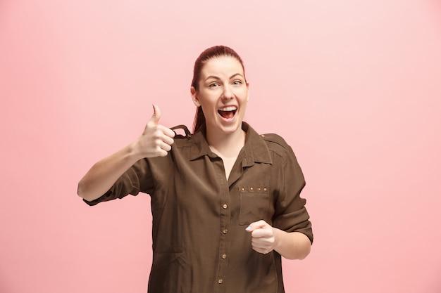 La femme d'affaires heureux debout et souriant contre le mur rose.