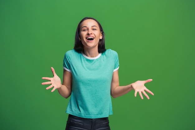 Femme d'affaires heureux debout et souriant isolé sur fond de studio vert. beau portrait de femme demi-longueur. jeune femme émotionnelle. les émotions humaines, le concept d'expression faciale. vue de face.