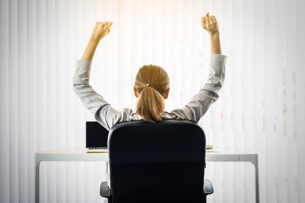 Femme d'affaires heureux étirer les bras en l'air et se détendre assis sur une chaise noire