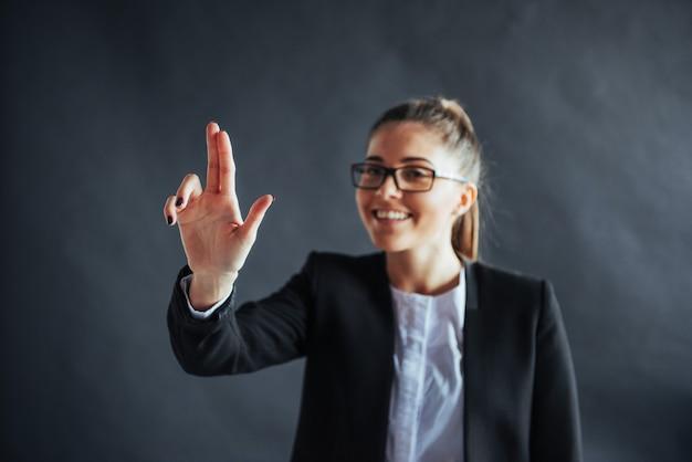 Femme d'affaires heureux montre le doigt vers le haut, debout sur un fond noir dans le, amical, souriant, se concentrer sur la main.