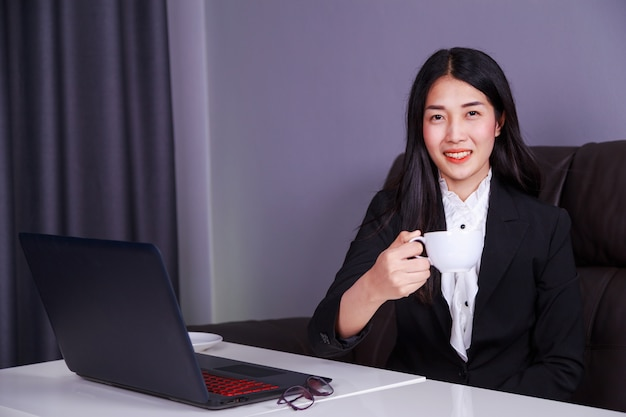 Femme d'affaires heureux travaillant sur ordinateur portable et boire une tasse de café