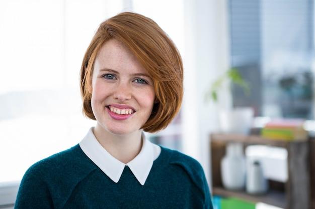 Femme d'affaires hipster souriant, debout dans son bureau