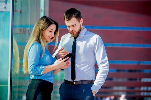 Femme d'affaires et homme d'affaires avec mobilephon planant un travail