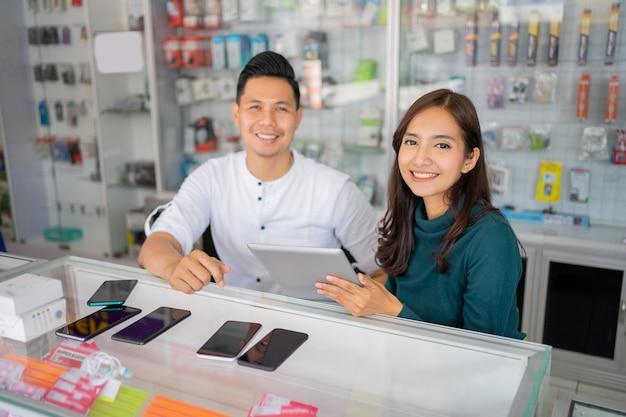 Une femme d'affaires et un homme d'affaires souriant à la caméra tout en utilisant une tablette ensemble