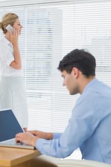Femme d'affaires et homme à l'aide de téléphone portable et ordinateur portable au bureau