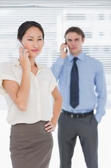 Femme d'affaires et homme à l'aide de téléphones portables au bureau
