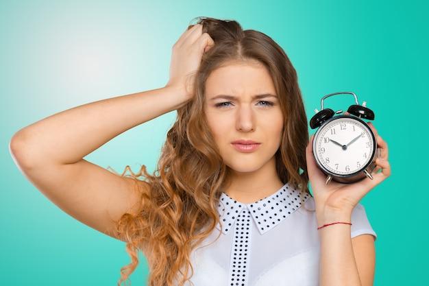 Femme d'affaires avec une horloge étant en retard pour ses livrables