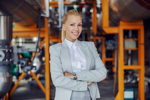 Femme d'affaires indépendante confiante en costume debout dans une installation de chauffage avec les bras croisés.