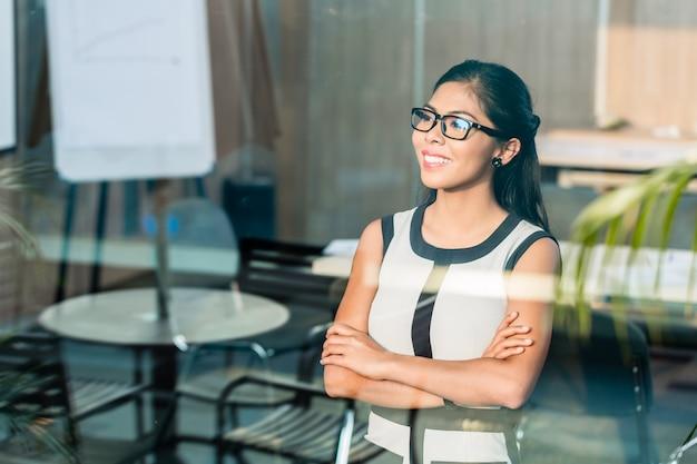 Femme d'affaires indonésienne à la fenêtre du bureau