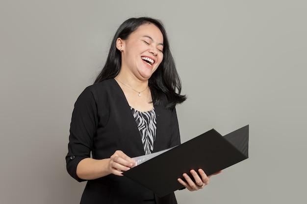 Femme d'affaires indonésienne riant tout en tenant le dossier