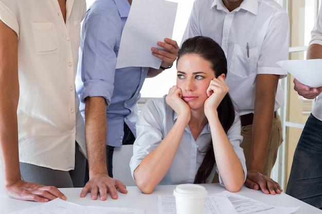 Femme d'affaires inquiète entourée de collègues