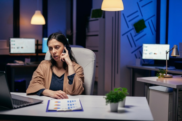 Femme d'affaires inquiète parlant avec des clients au cours d'une conversation sur smartphone. femme entrepreneur travaillant tard le soir dans une entreprise faisant des heures supplémentaires au cours d'un appel téléphonique.