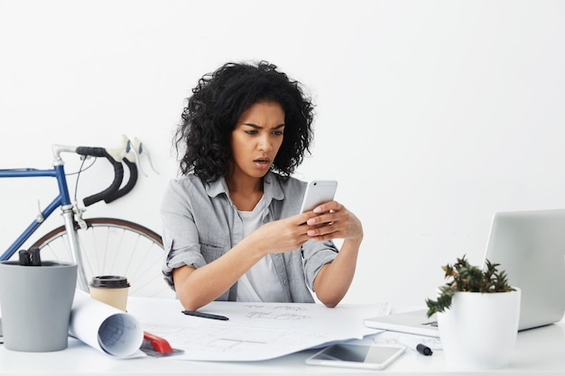 Femme d'affaires insatisfaite avec une peau foncée et des cheveux volumineux assis à son bureau