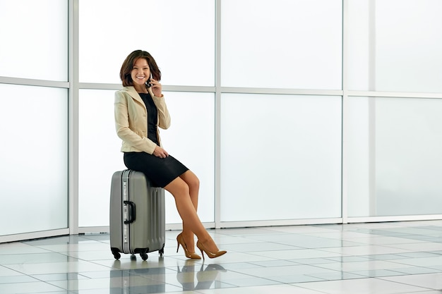 Femme d'affaires jeune à l'aéroport avec sac de chariot à bagages, parler au téléphone et souriant.