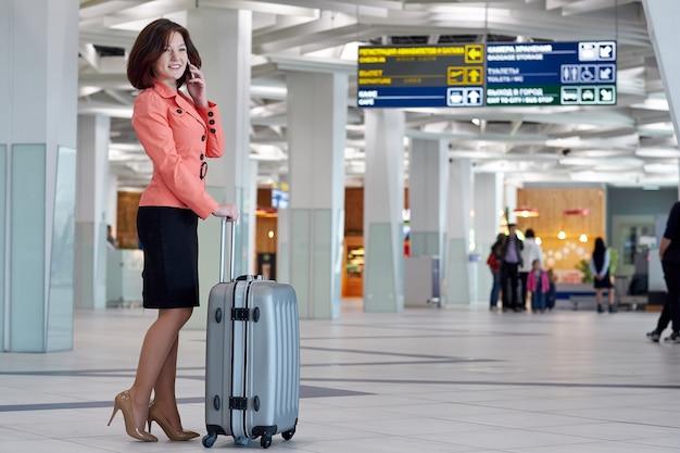 Femme d'affaires jeune à l'aéroport avec sac de chariot, parler au téléphone et souriant.
