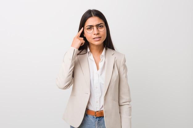 Femme d'affaires jeune arabe isolé blanc montrant un geste de déception avec l'index.