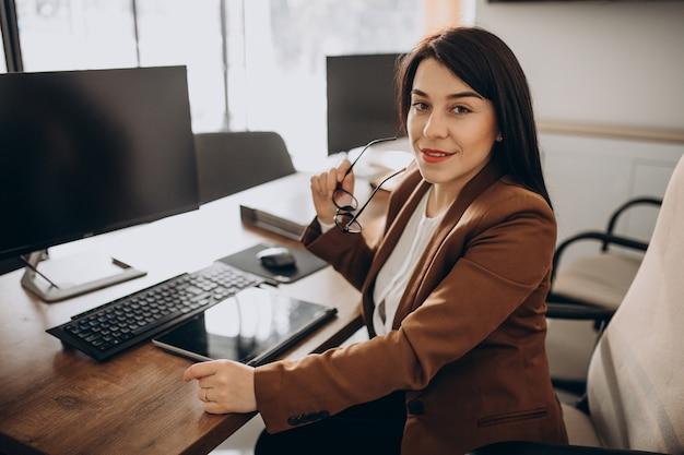 Femme d'affaires jeune assis au bureau et travaillant sur ordinateur