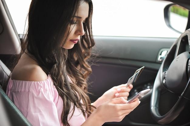 Femme d'affaires jeune assis dans la voiture à l'aide de téléphone portable.