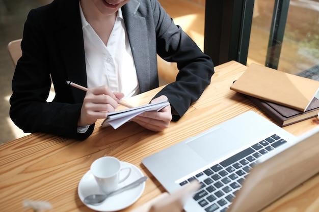 Femme d'affaires jeune assis à table et prendre des notes dans un ordinateur portable sur un bureau en bois.