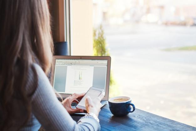 Femme d'affaires jeune attractif travaillant sur ordinateur portable au café.