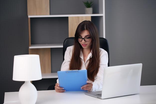 Femme d'affaires jeune brune avec ordinateur portable au bureau.