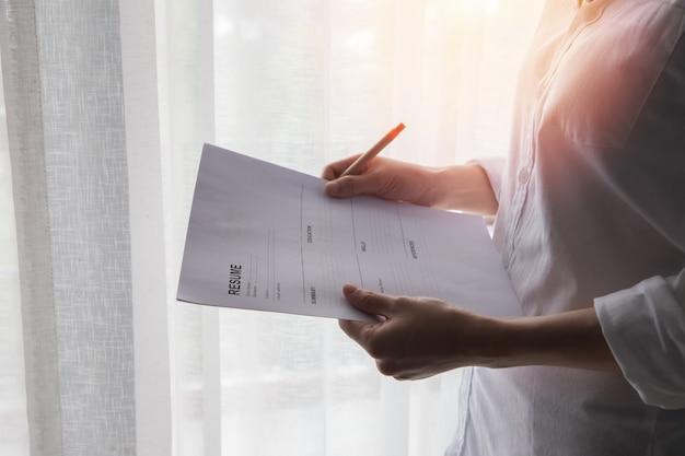 Femme d'affaires jeune en chemise blanche remplissant forme de cv, concept de trouver un emploi à la maison.