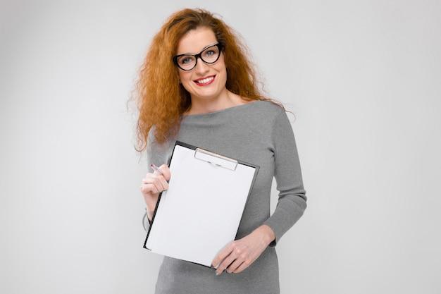 Femme d'affaires jeune dans des vêtements gris dans des verres en tenant le presse-papiers sur le mur gris