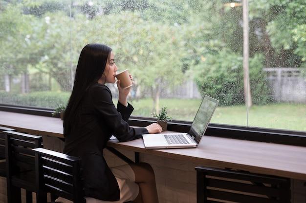 Femme d'affaires jeune faire une pause avec du café tout en travaillant sur ordinateur portable au bureau