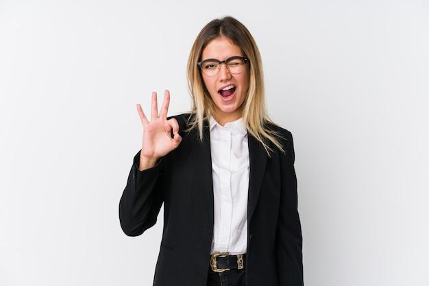 Femme d'affaires jeune fait un clin d'œil et détient un geste correct avec la main.